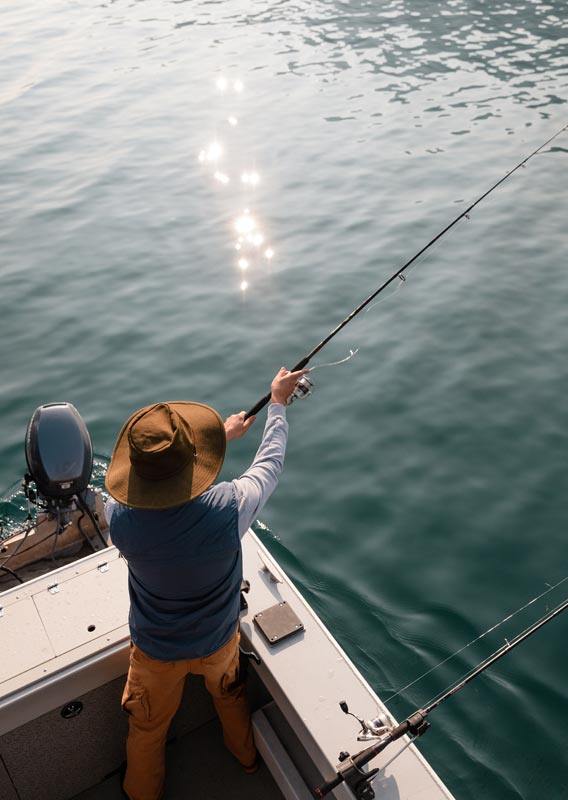An angler casts a fishing rod into a lake off the back of a motor boat.