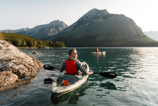 Two kayakers paddle on a lake below forested mountains