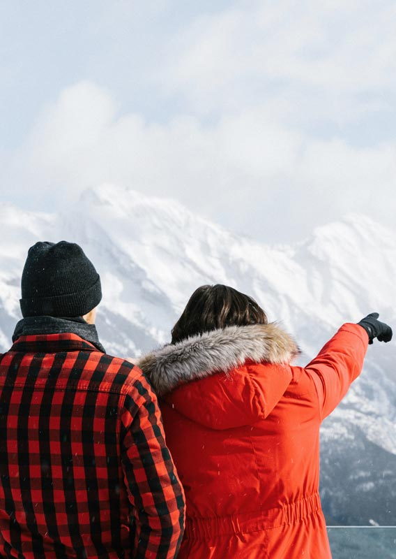 Two people look out from a viewpoint towards snow-covered mountains.