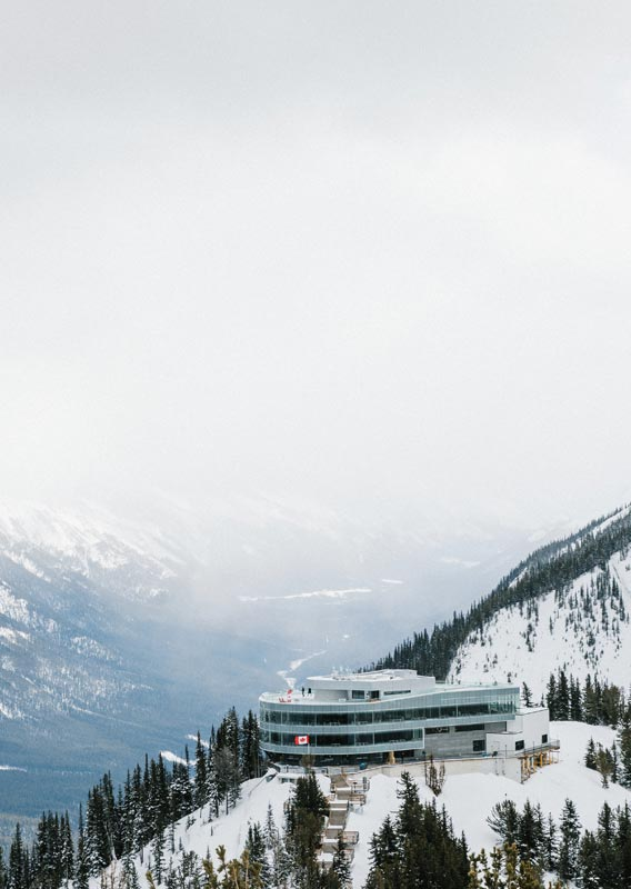 The Banff Gondola summit building atop Sulphur Mountain above a snowy valley.