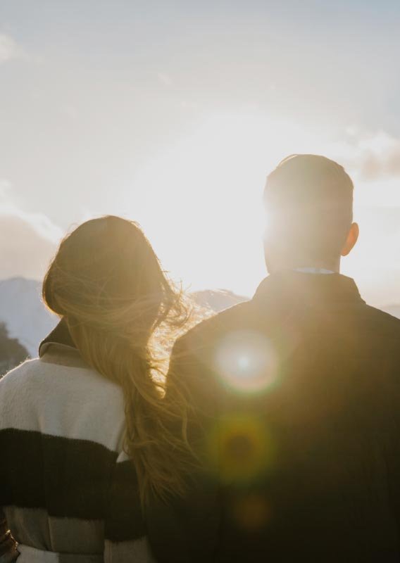 Two people look towards the sun setting behind snow-covered mountains.