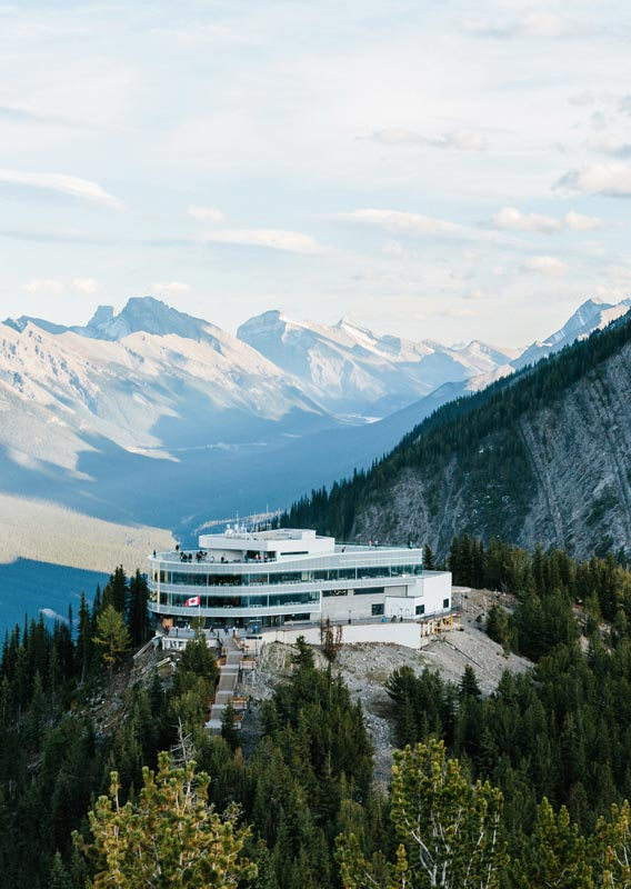 An aerial view of the Banff Gondola summit building, mountains and a deep valley