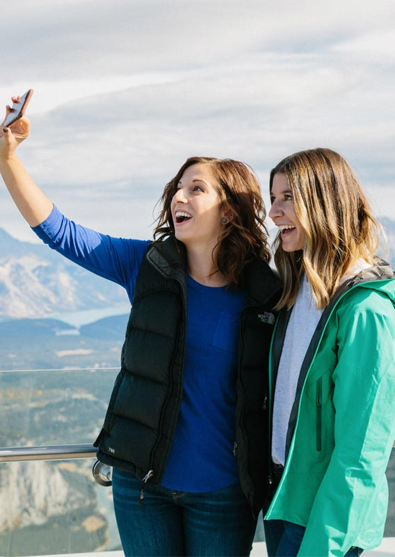 Two people take a selfie at the top of the Banff Gondola