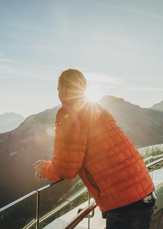 A person in an orange jacket stands at a balcony railing looking towards a mountain.