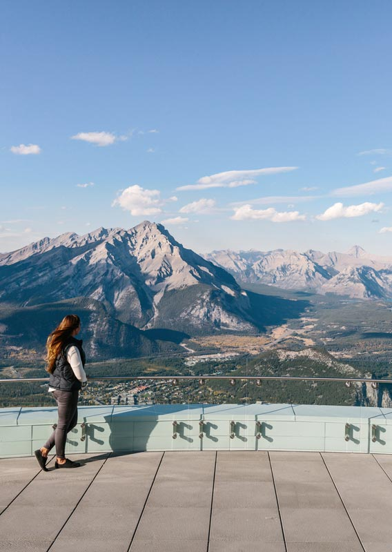 A woman looks out at mountains and forests from the top of the Banff Gondola.