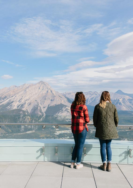 Two people look out towards a mountain landscape from the top of the Banff Gondola.