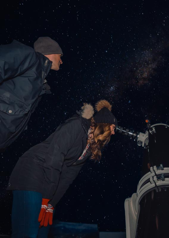 A person looks through a telescope while another stands to the side stargazing.