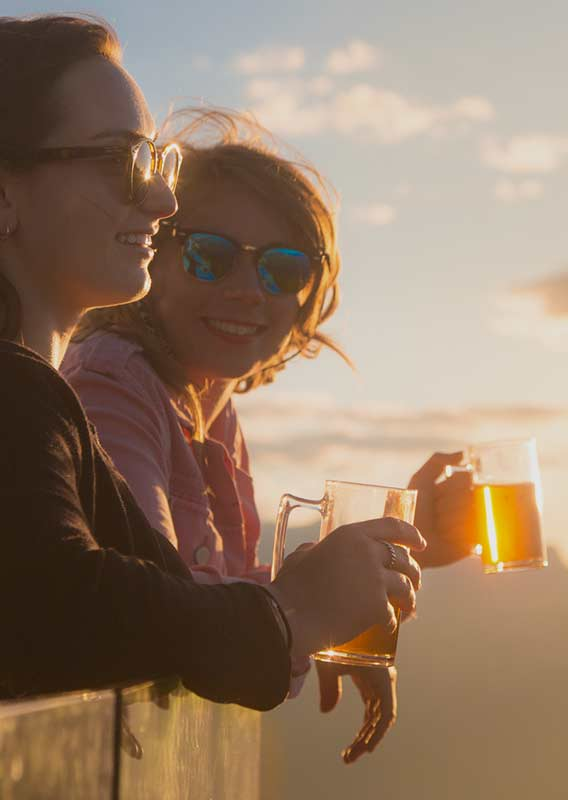 Woman stands overlooking mountain views holding a beer in the golden light of sunset