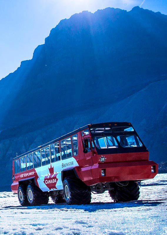 A red and white bus beneath mountains on a field of ice