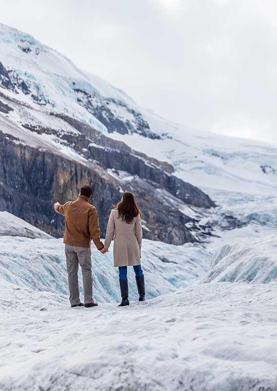 Couple walking along a glacier looking towards mountains.