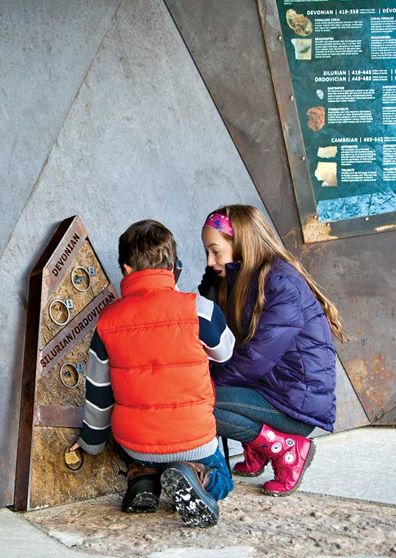 Children exploring the interpretive area of the Glacier Skywalk listening to the audio tour