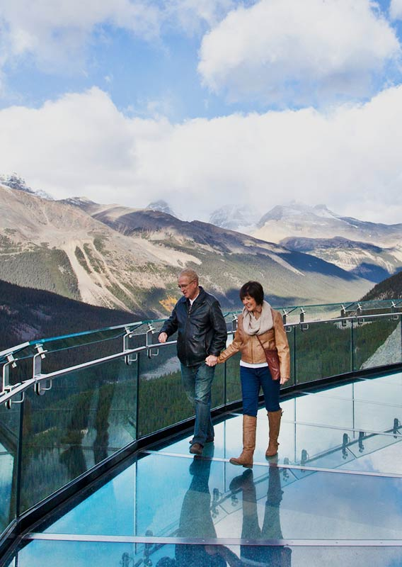 Couple walking on the transparent glass of the Columbia Icefield Skywalk