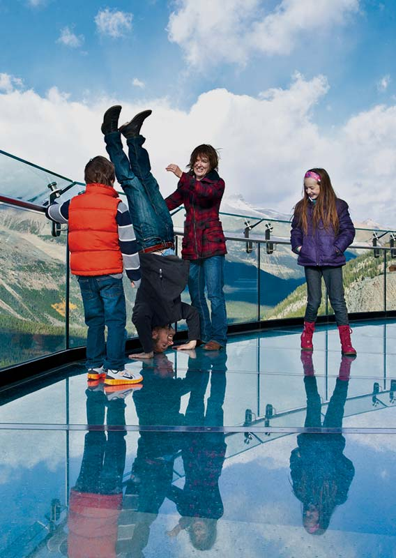 Family on the glass of the Columbia Icefield Skywalk watching father do a handstand
