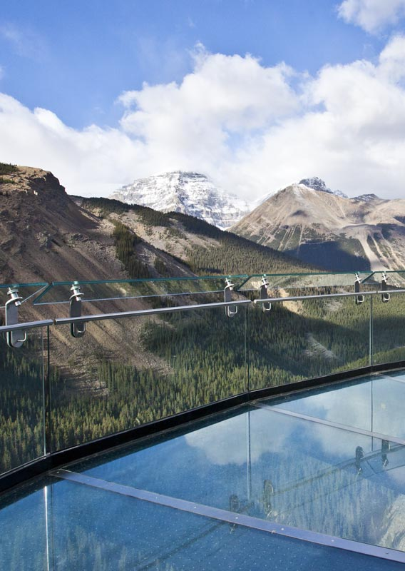 A view towards tree and snow-capped mountains from a glass platform.