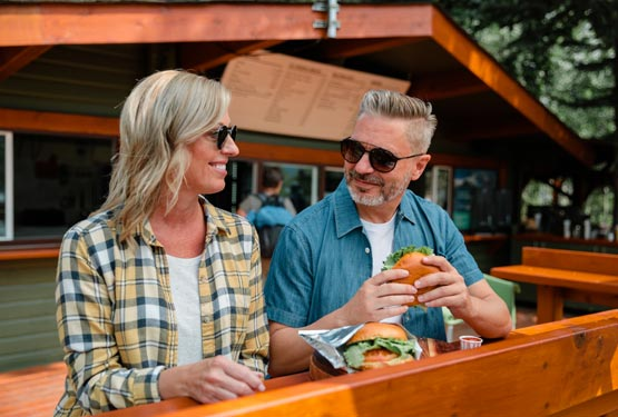 Two people enjoy hamburgers at a patio edge table.