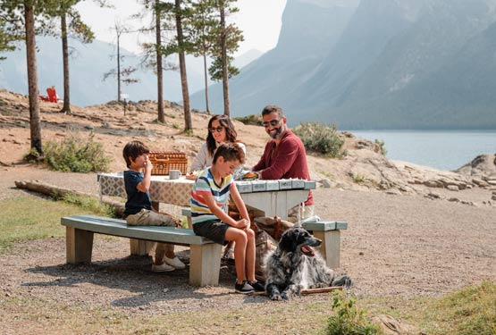 A family sits at a picnic table next to a mountain lake