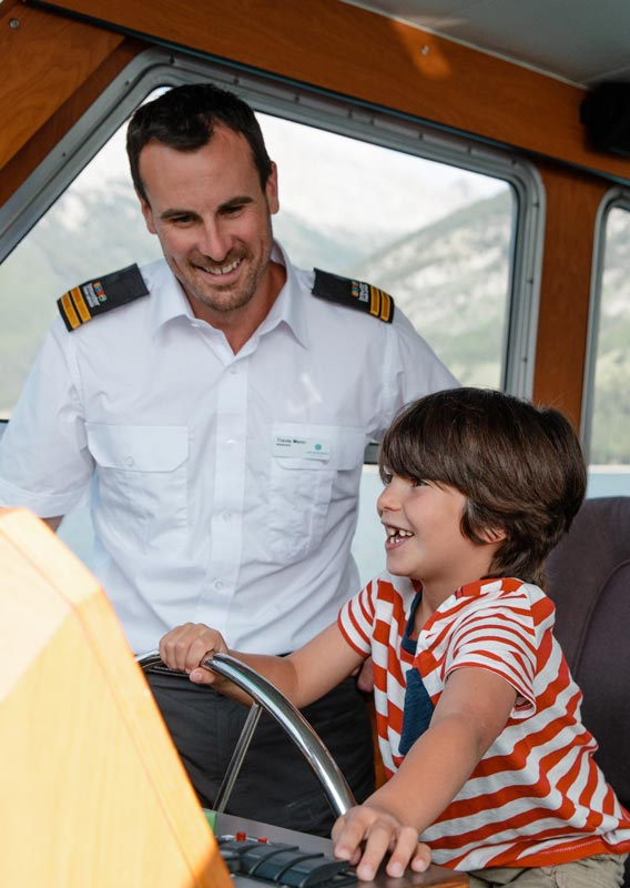 A boy sits at the captains chair of a boat while the captain stands aside