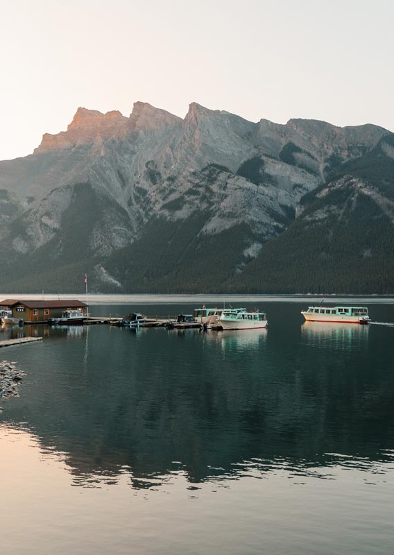 A few boats around a dock extending out on a calm lake below rocky mountains.