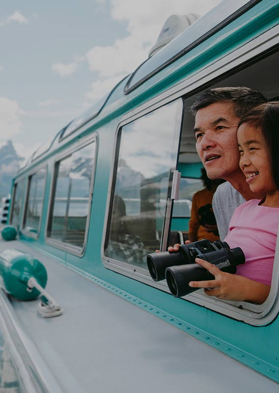 A father and his young daughter are looking out window of Maligne Lake Cruise holding binoculars
