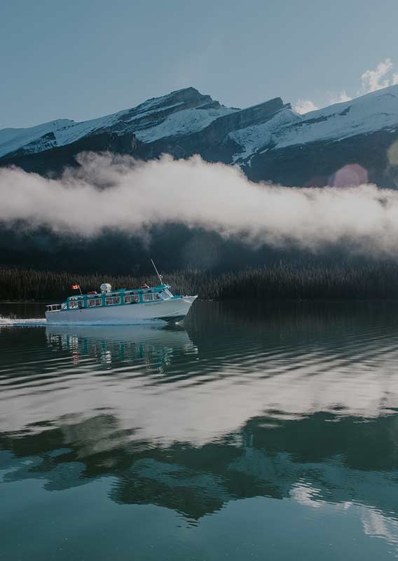 Maligne Lake Cruise Boat travels across lake reflecting low cloud and mountains