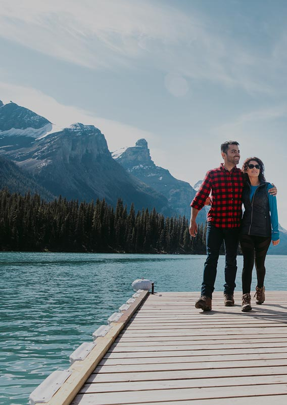 Couple walk on dock as they depart the Maligne Lake Cruise boat