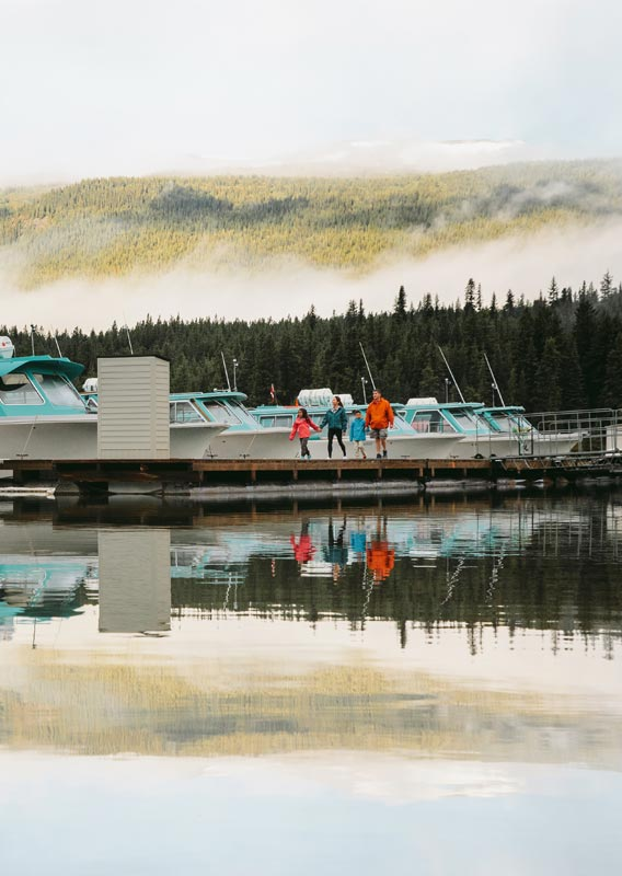 A family walks on a dock alongside a set of docked boats below a forested mountainside.