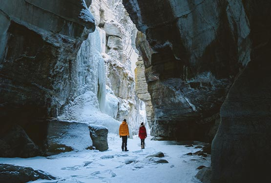 Two people walk through an icy canyon