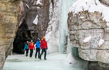 A group of people walking through an icy canyon.