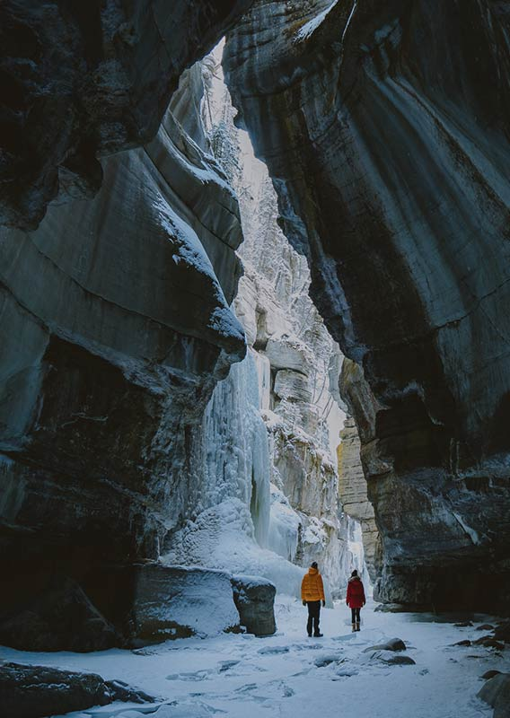 Two people stand at the frozen bottom of Maligne Canyon in front of frozen waterfall