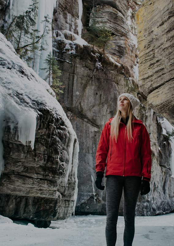 A woman in a red jacket stands in an icy canyon