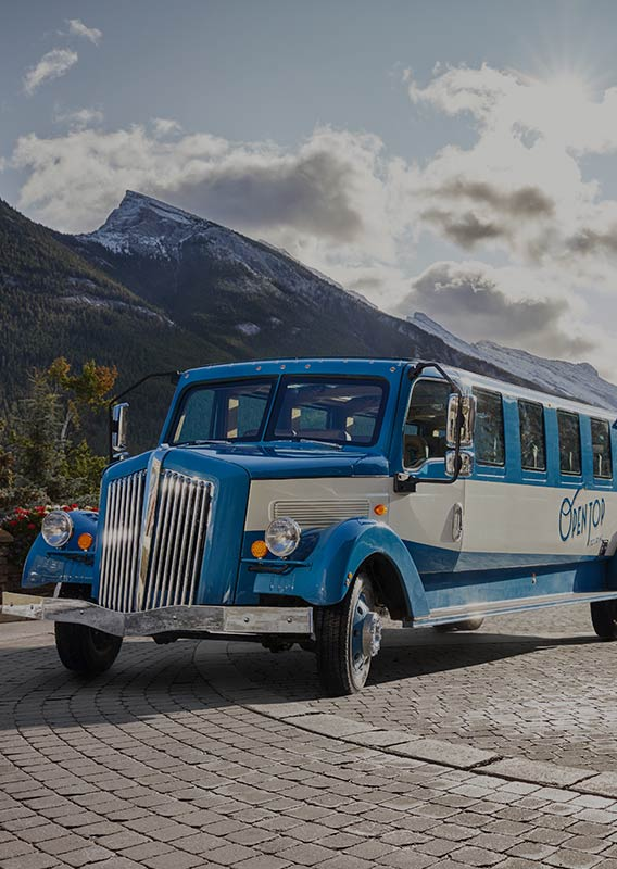 A historic style bus parked in front of a stone building and snow-capped mountains.