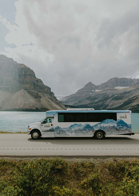 Brewster Express bus travels past Bow Lake on a summers day