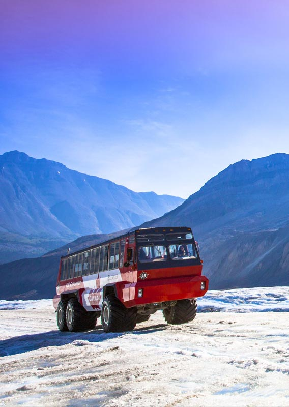 A red and white Ice Explorer drives down a glacier before a blue and purple sky.