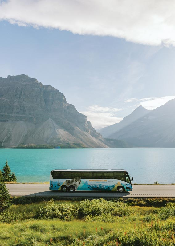 A blue coach bus drives along a road next to a clear blue lake below mountains.