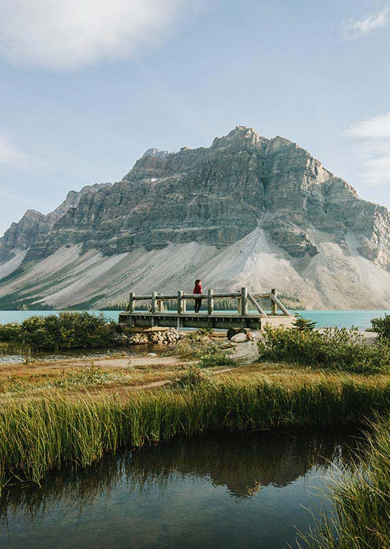 A person stands on a wooden bridge alongside a blue lake and soaring mountain.