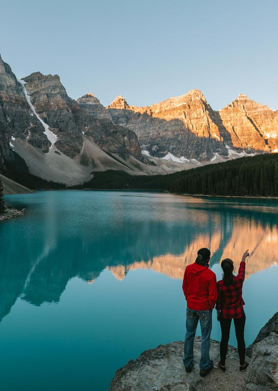Two people stand above Moraine Lake, looking at mountains.