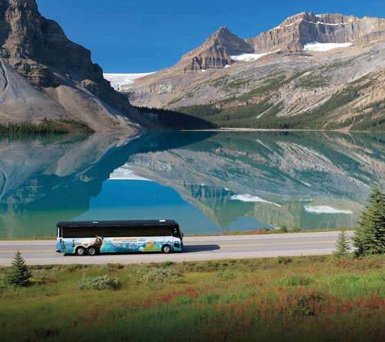 A coach bus drives alongside a blue mountain lake