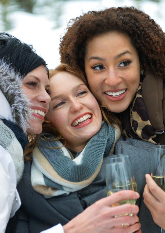Four people, smiling and bundled in winter jackets, group together to take a selfie.