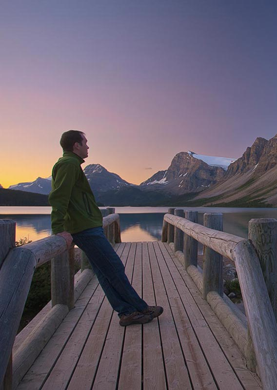 A man stands on a small wooden footbridge looking out to a mountain across a calm lake.