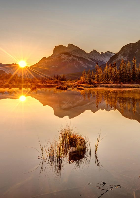 The sun rises from behind a horizon of mountains, shining off of a calm lake.