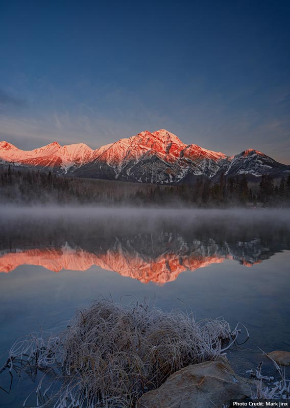 A view across a misty lake toward a snow-dusted mountain.
