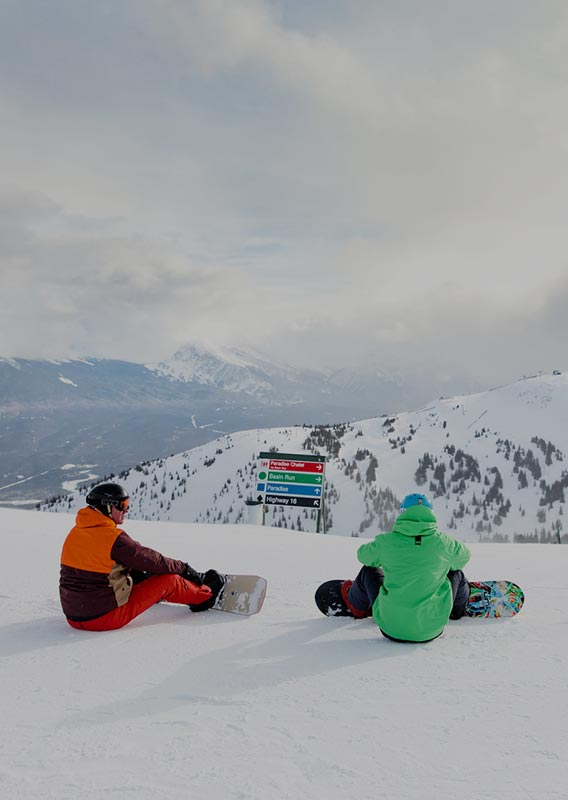 Three snowboarders sit on a mountaintop.