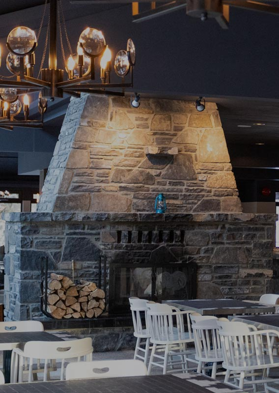A dining room with a large stone fireplace