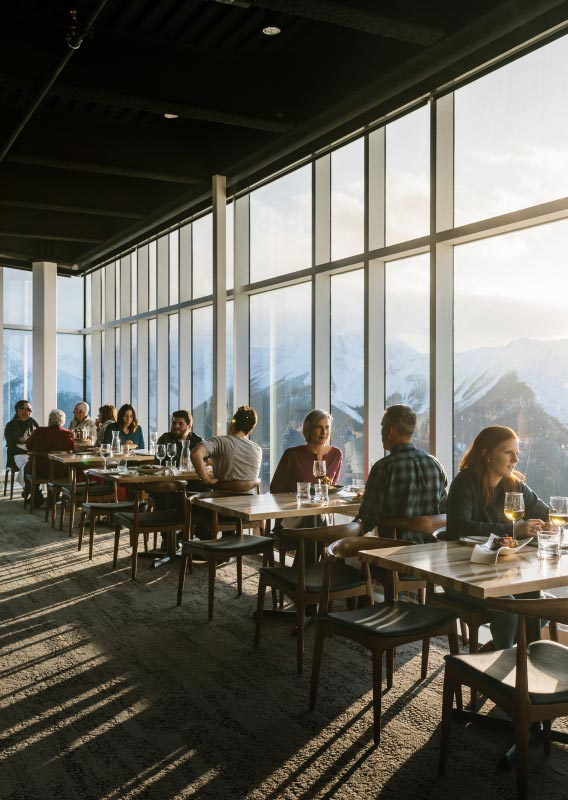 A dining room with floor-to-ceiling windows looks out onto snow-capped mountains.