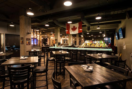Toque Restaurant interior, showing tables and a Canadian Flag above the bar