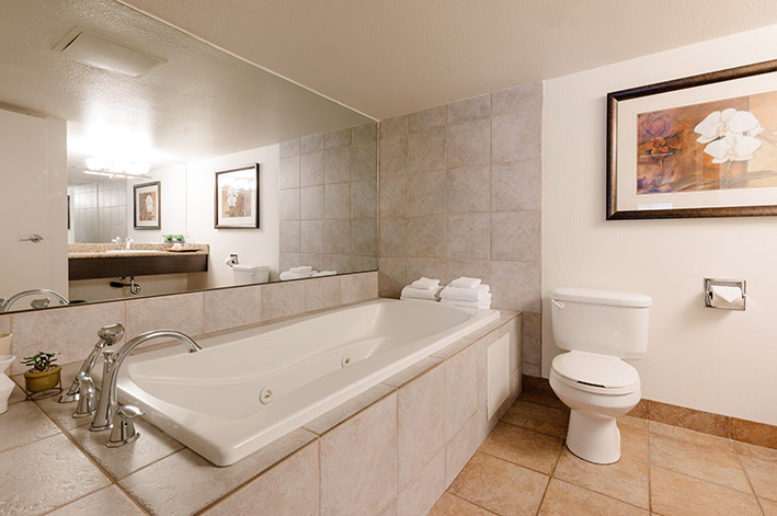 A tiled jetted tub with towels next to a toilet and large mirror