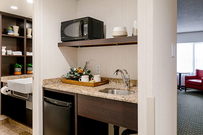 A bright kitchenette with microwave, mini fridge and sink