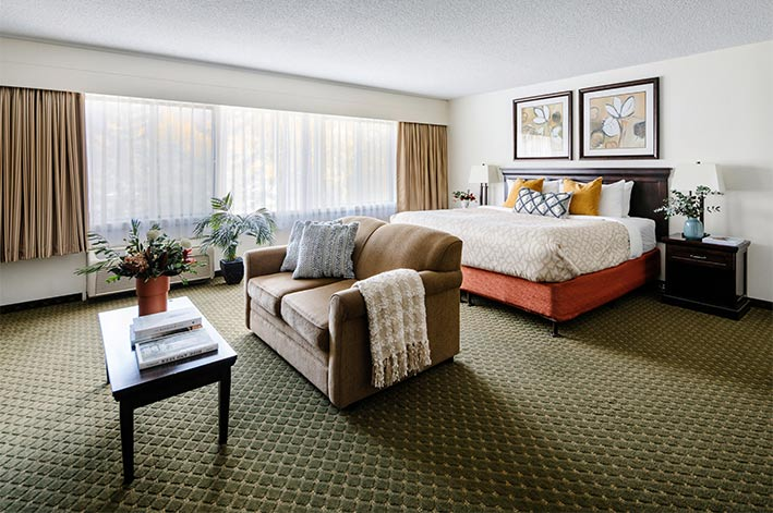 A king bed, couch and coffee table in a large hotel room