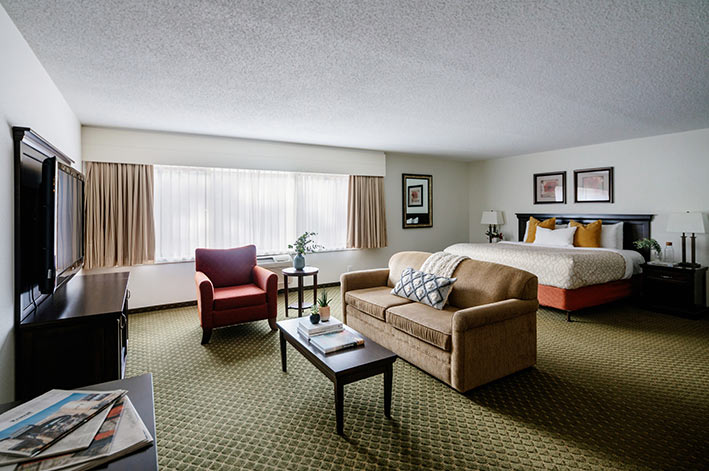 A large hotel suite with sofa, table and king bed