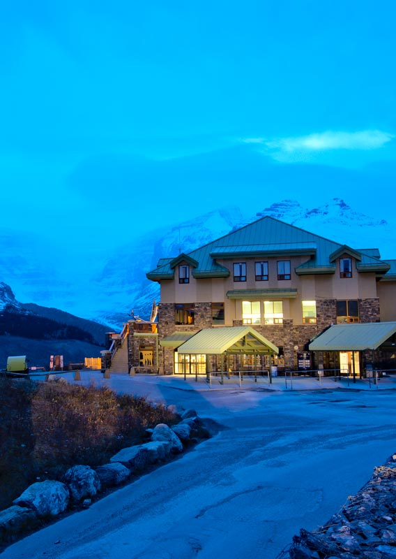 A hotel glows at dusk with snow-covered mountains in the background